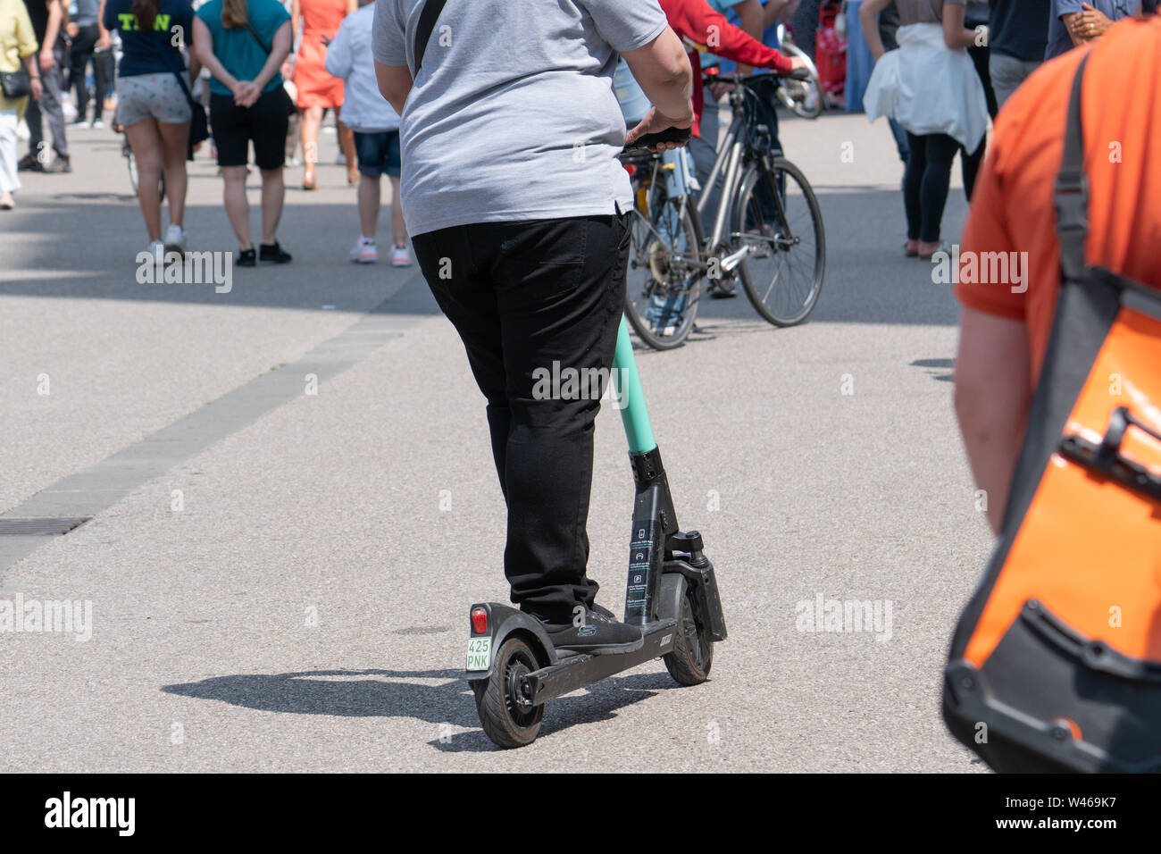 18 July 2019, Hessen, Frankfurt/Main: A man drives on a rented e-scooter through a busy pedestrian zone. Photo: Frank Rumpenhorst/dpa - Stock Image