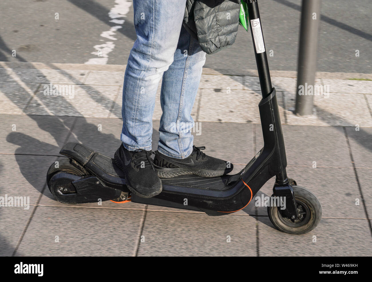 15 July 2019, Hessen, Frankfurt/Main: A man drives through the city centre on an e-scooter that has neither an operating permit nor an insurance number. Photo: Frank Rumpenhorst/dpa - Stock Image