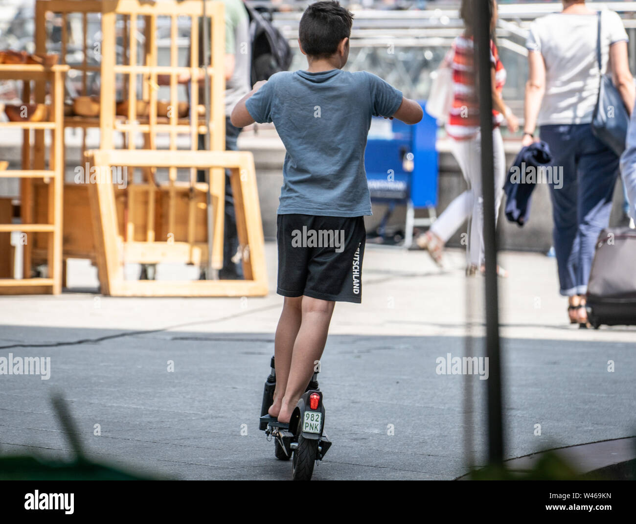 18 July 2019, Hessen, Frankfurt/Main: A little boy drives on a rented e-scooter through a busy pedestrian zone. Photo: Frank Rumpenhorst/dpa - Stock Image