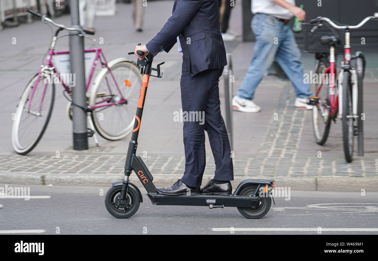 15 July 2019, Hessen, Frankfurt/Main: A man in a suit drives on a rented e-scooter through the city centre on a street. Photo: Frank Rumpenhorst/dpa - Stock Image