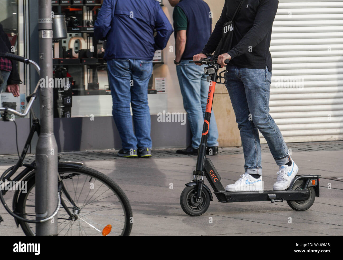 15 July 2019, Hessen, Frankfurt/Main: A man drives on a rented e-scooter on the sidewalk in the city center. Photo: Frank Rumpenhorst/dpa - Stock Image