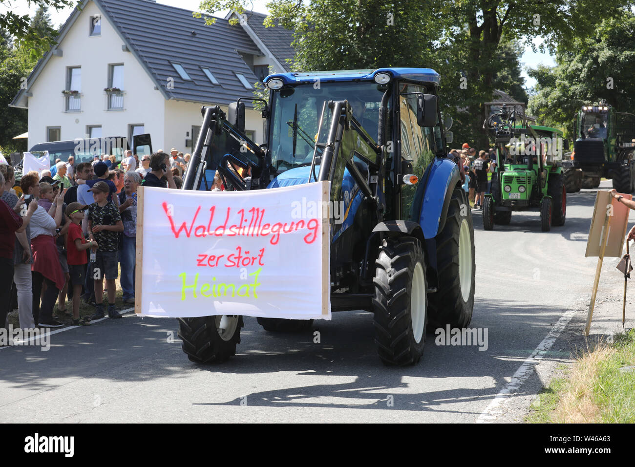 20 July 2019, Thuringia, Wurzbach-Rodacherbrunn: A participant of a protest action against forest decommissioning in the Wurzbach area drives with his tractor during a demonstration drive. In the forest areas around Rodacherbrunn, a 1400 hectare spruce forest is to be abandoned for forestry purposes. The organizers of the action fear that this would sacrifice the forest to the bark beetle. Photo: Bodo Schackow/dpa-Zentralbild/dpa - Stock Image