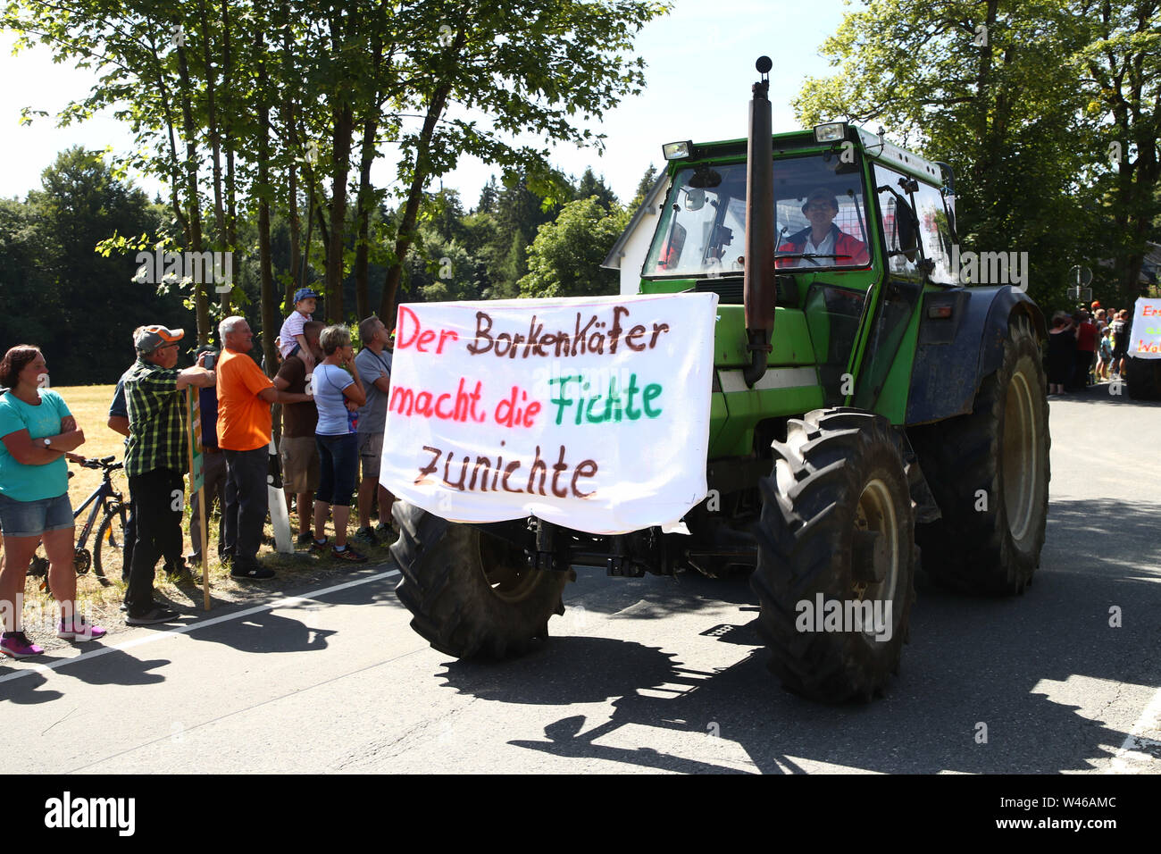 Wurzbach Rodacherbrunn, Germany. 20th July, 2019. A participant of a protest action against forest decommissioning in the Wurzbach area drives with his tractor during a demonstration drive. In the forest areas around Rodacherbrunn, a 1400 hectare spruce forest is to be abandoned for forestry purposes. The organizers of the action fear that this would sacrifice the forest to the bark beetle. The poster says: The bark beetle destroys the spruce. Credit: Bodo Schackow/dpa-Zentralbild/dpa/Alamy Live News - Stock Image