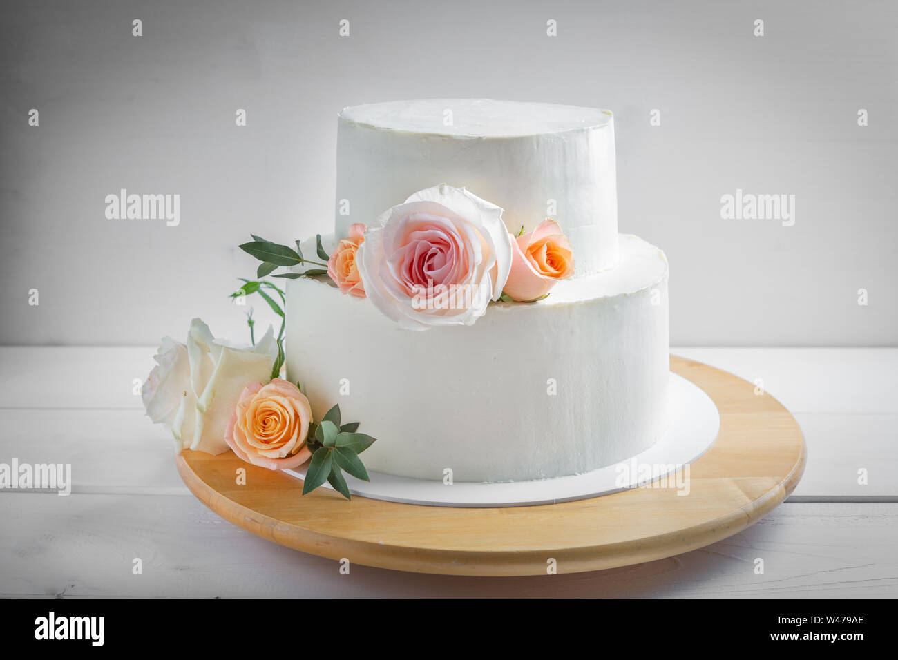 White Wedding Two Tiered Cake Decorated With Flowers With Green Leaves In A Rustic Style Stock Photo Alamy