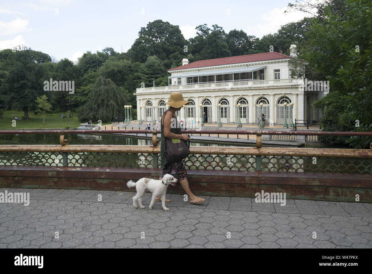 Woman walks her dog over the  Lullwater Bridge by the historic Boathouse which houses the Audubon Society in Prospect Park, Brooklyn, New York. Stock Photo