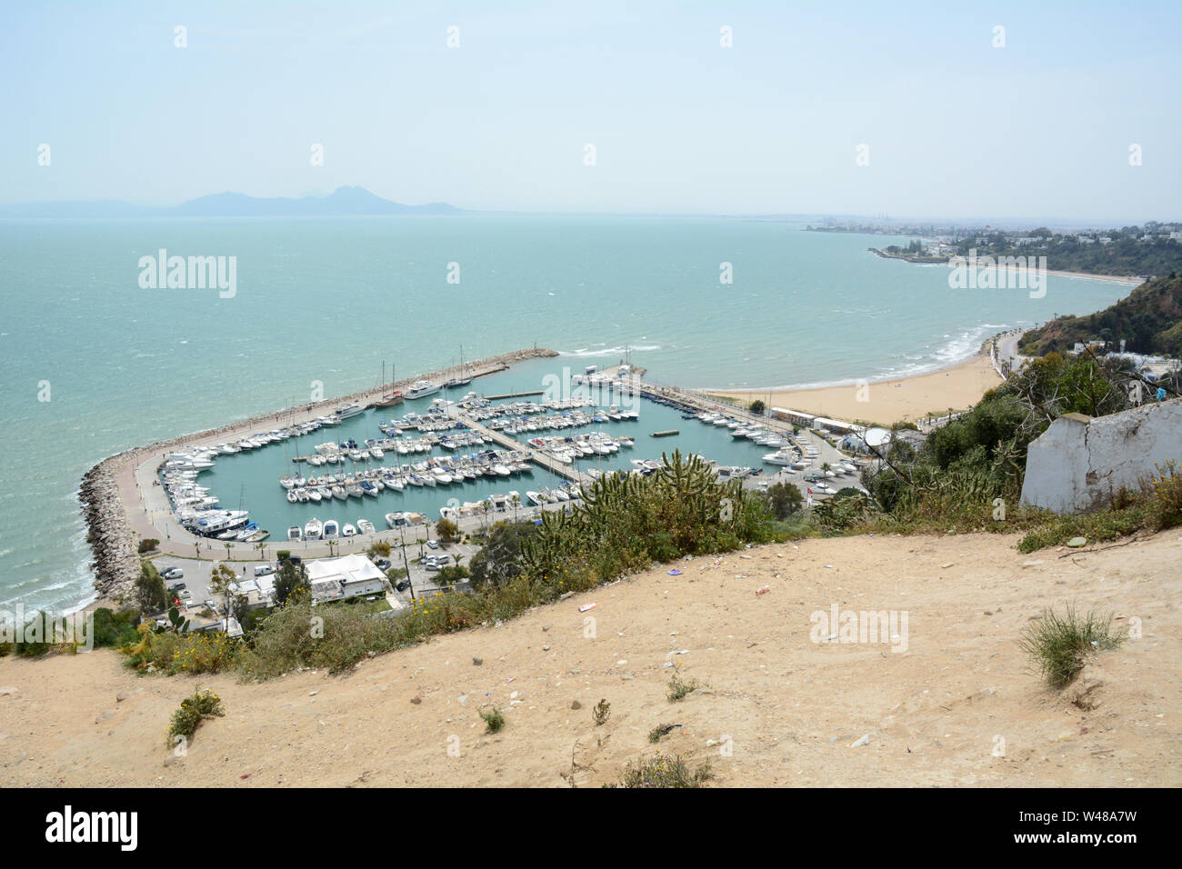 A hillside viewpoint overlooking the aquamarine Mediterranean Sea and boat harbour in the suburb of Sidi Bou Said, Tunis, Tunisia. Stock Photo