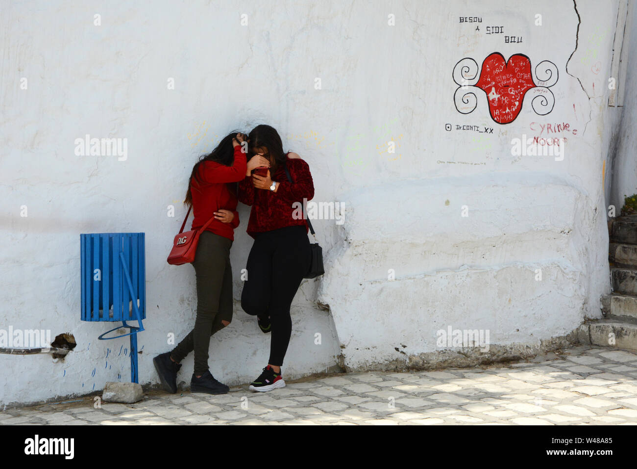 Two Tunisian female teens gaze at a cellphone in the shade of alley in the pedestrian zone in the tourist town of Sidi Bou Said, near Tunis, Tunisia. Stock Photo
