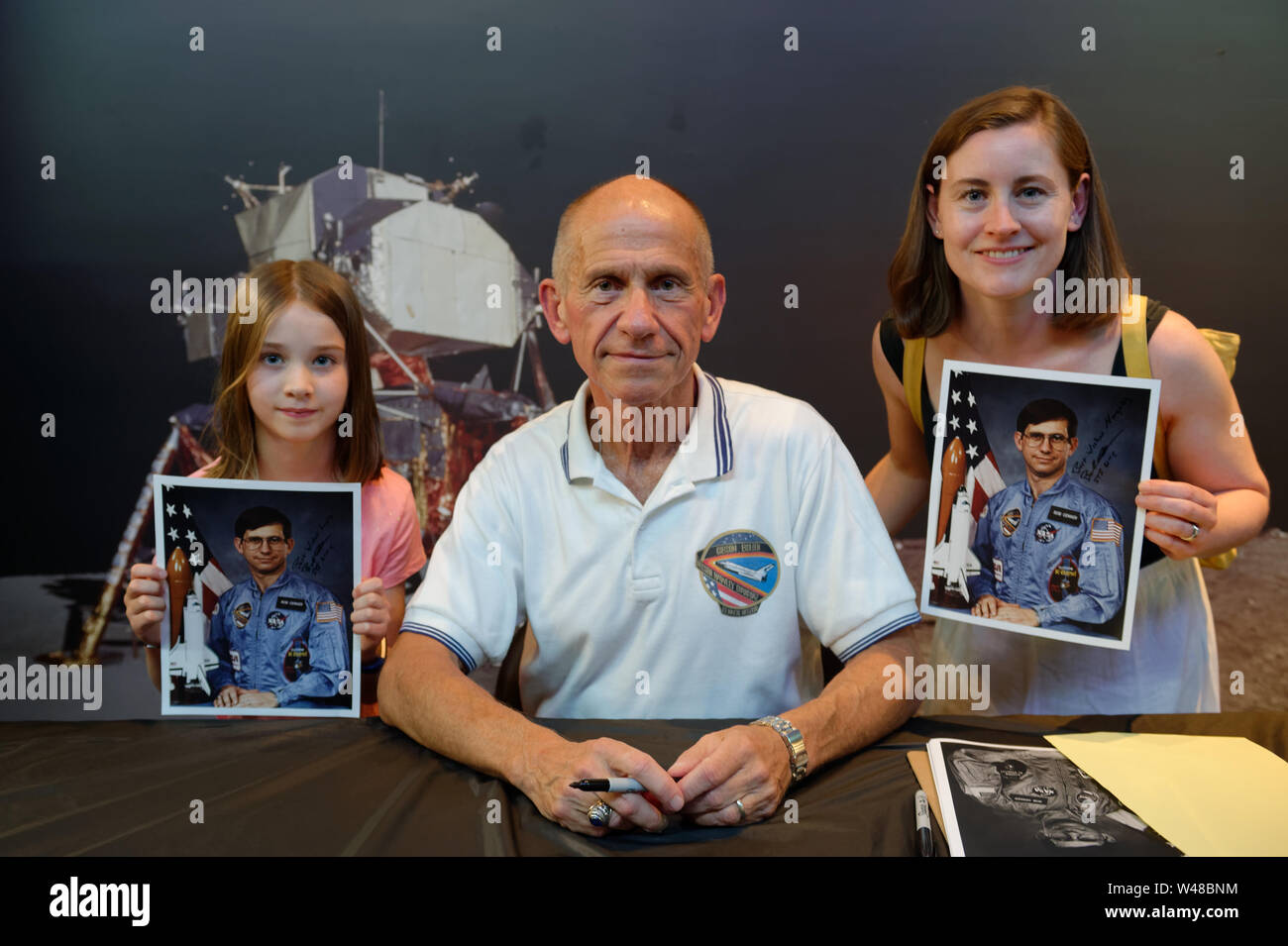 Garden City, New York, USA. 20th July, 2019. At center, NASA Space Shuttle astronaut BOB CENKER poses with, at left, LUCY DEEGAN, 8, and MEREDITH DEEGAN, both of Swords, a town near Dublin, Ireland, at the Moon Fest Apollo at 50 Countdown Celebration at Cradle of Aviation Museum in Long Island, held at the same time the Apollo 11 Lunar Module, The Eagle, landed on the Moon 50 years ago. Deegan free up in Greenlawn, NY. Credit: Ann Parry/ZUMA Wire/Alamy Live News - Stock Image