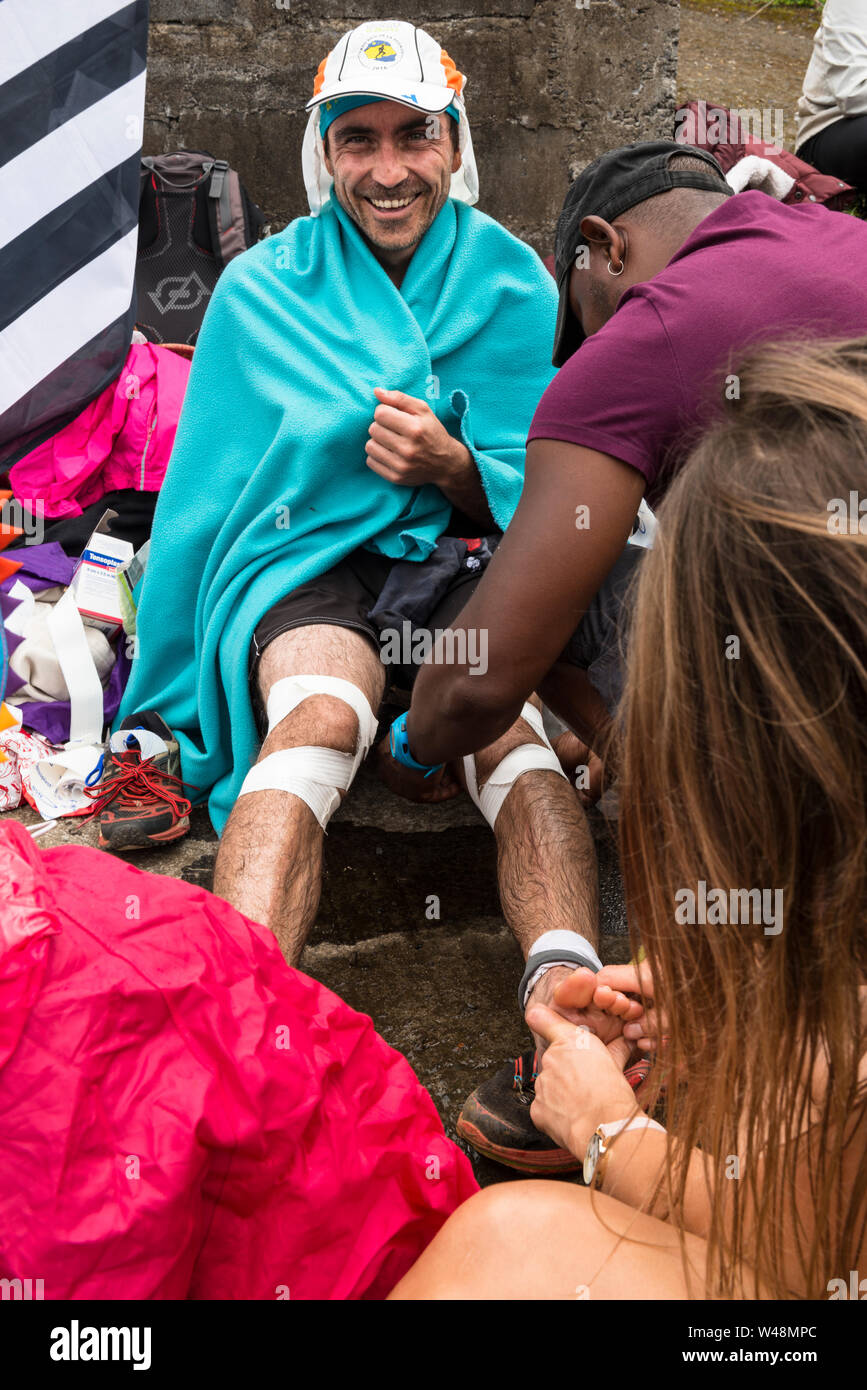 Running repairs! An injured runner puts on a brave face as he receives treatment at a roadside first aid station during the Grand Raid, Reunion Stock Photo