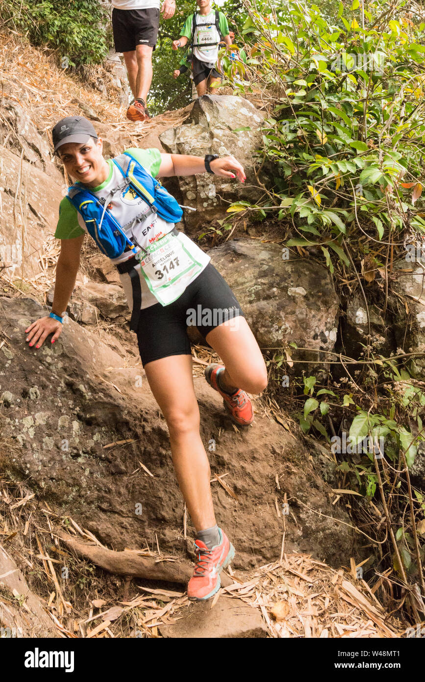 Competitor on the steep rough track from les Deux Bras in the Cirque de Mafate during the Grand Raid, Reunion Stock Photo