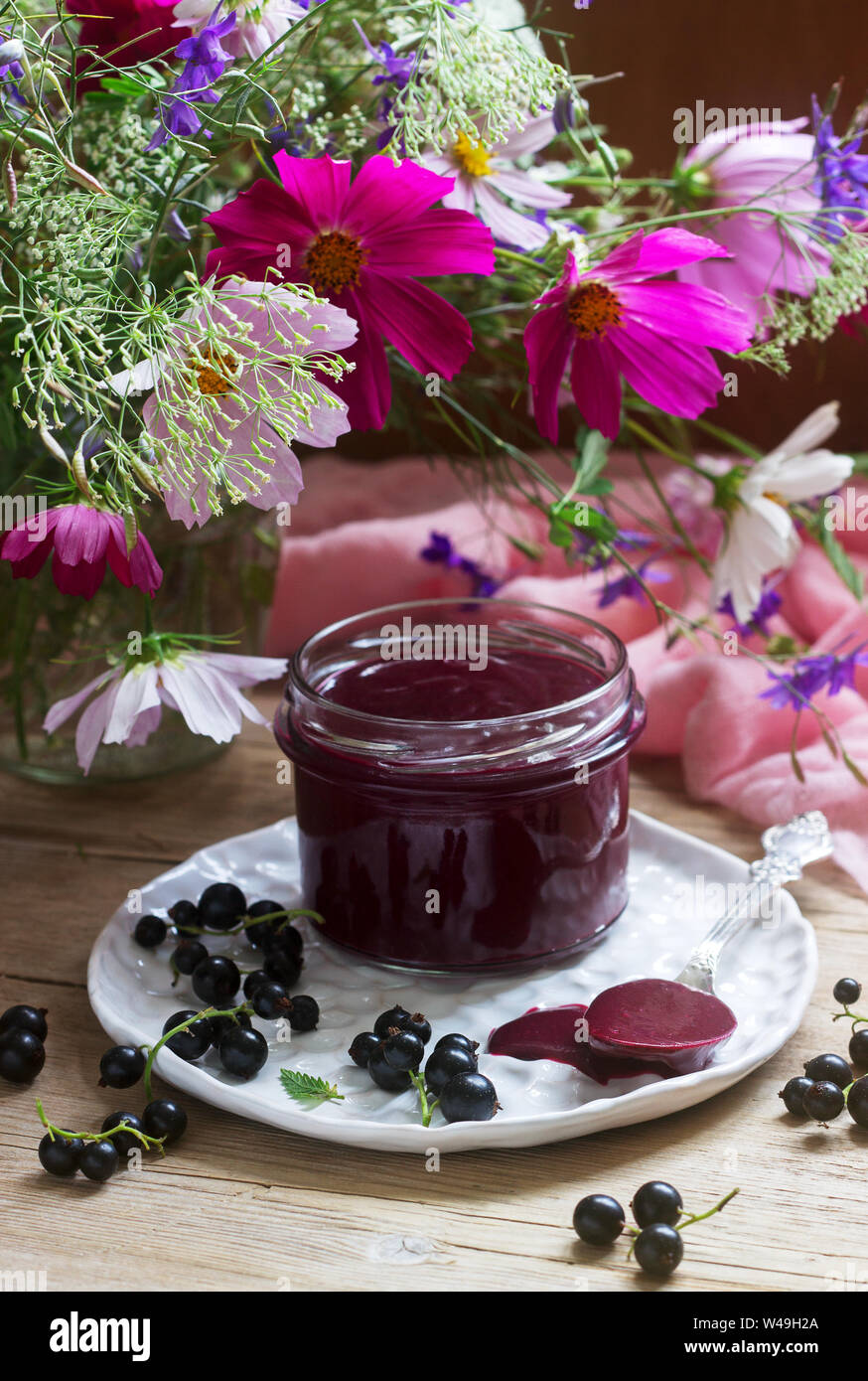 Black currant custard, currants and a bouquet of wild flowers on a wooden background. Rustic style. Stock Photo