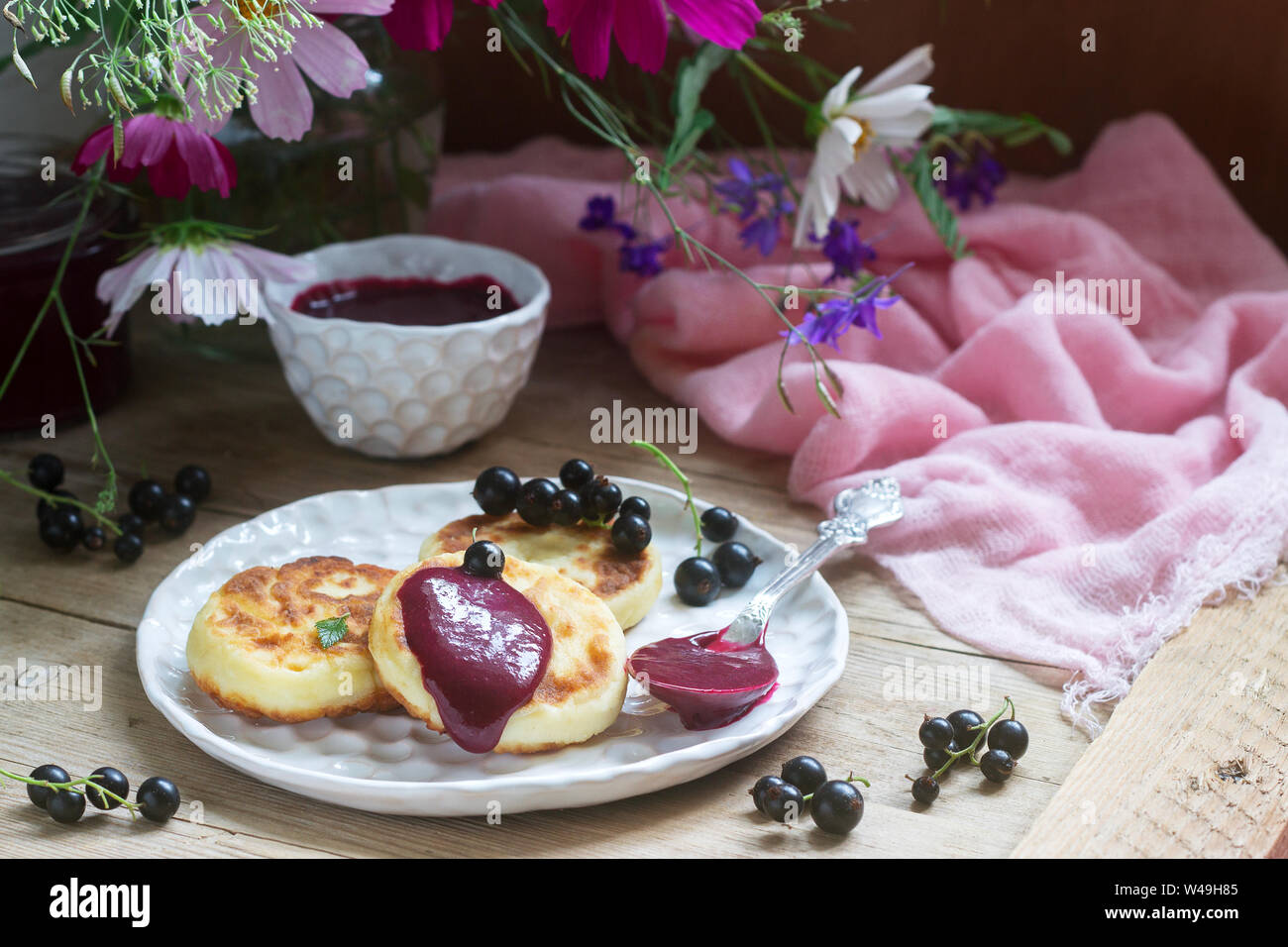 Breakfast of quark pancakes, black currant custard, currants and a bouquet of wild flowers on a wooden background. Stock Photo