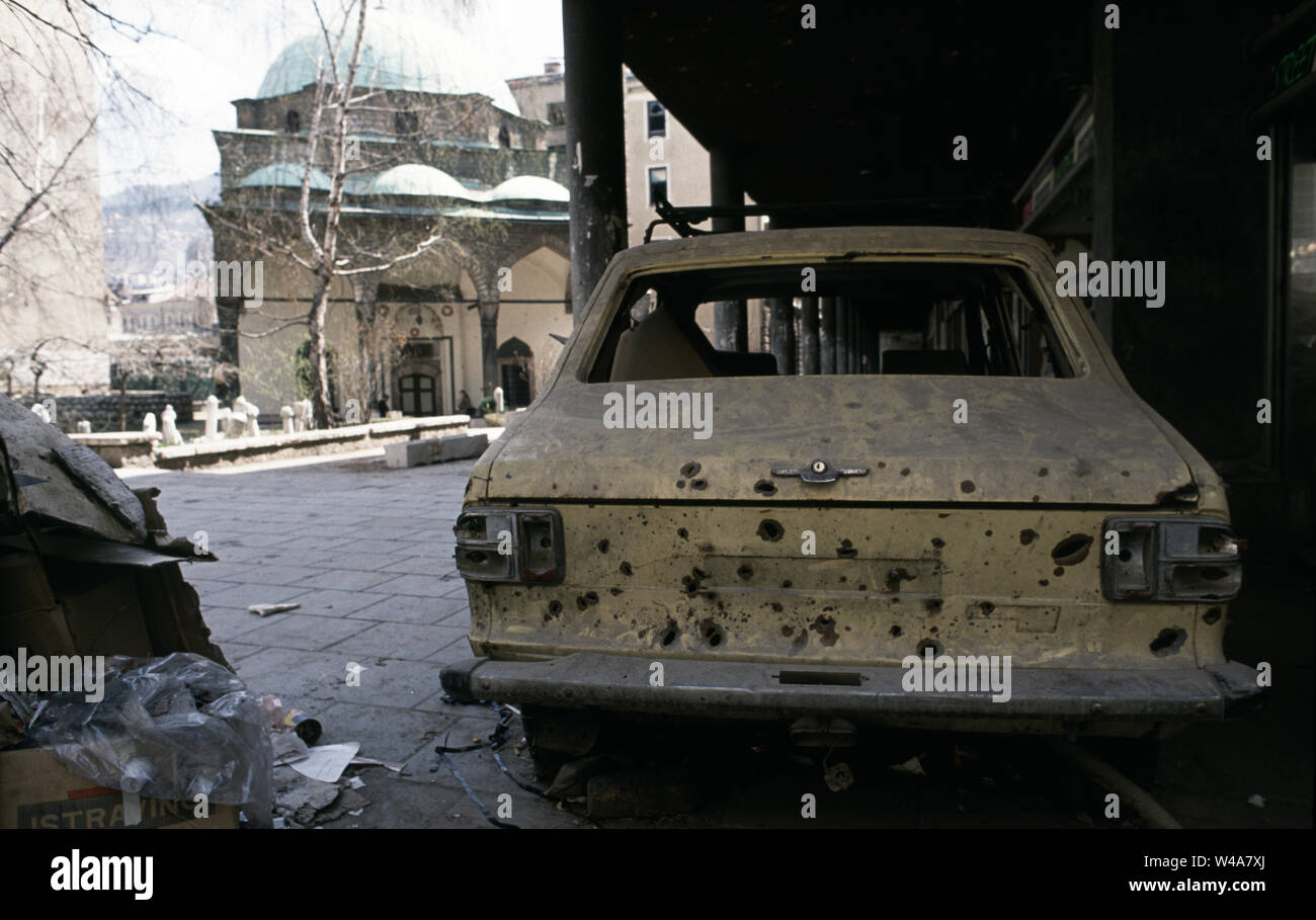 21st April 1993 During the Siege of Sarajevo: a car riddled with mortar bomb shrapnel 'parked in an arcade on Vase Miskina (today called Ferhadija Street). In the background is the Ferhadija mosque. - Stock Image