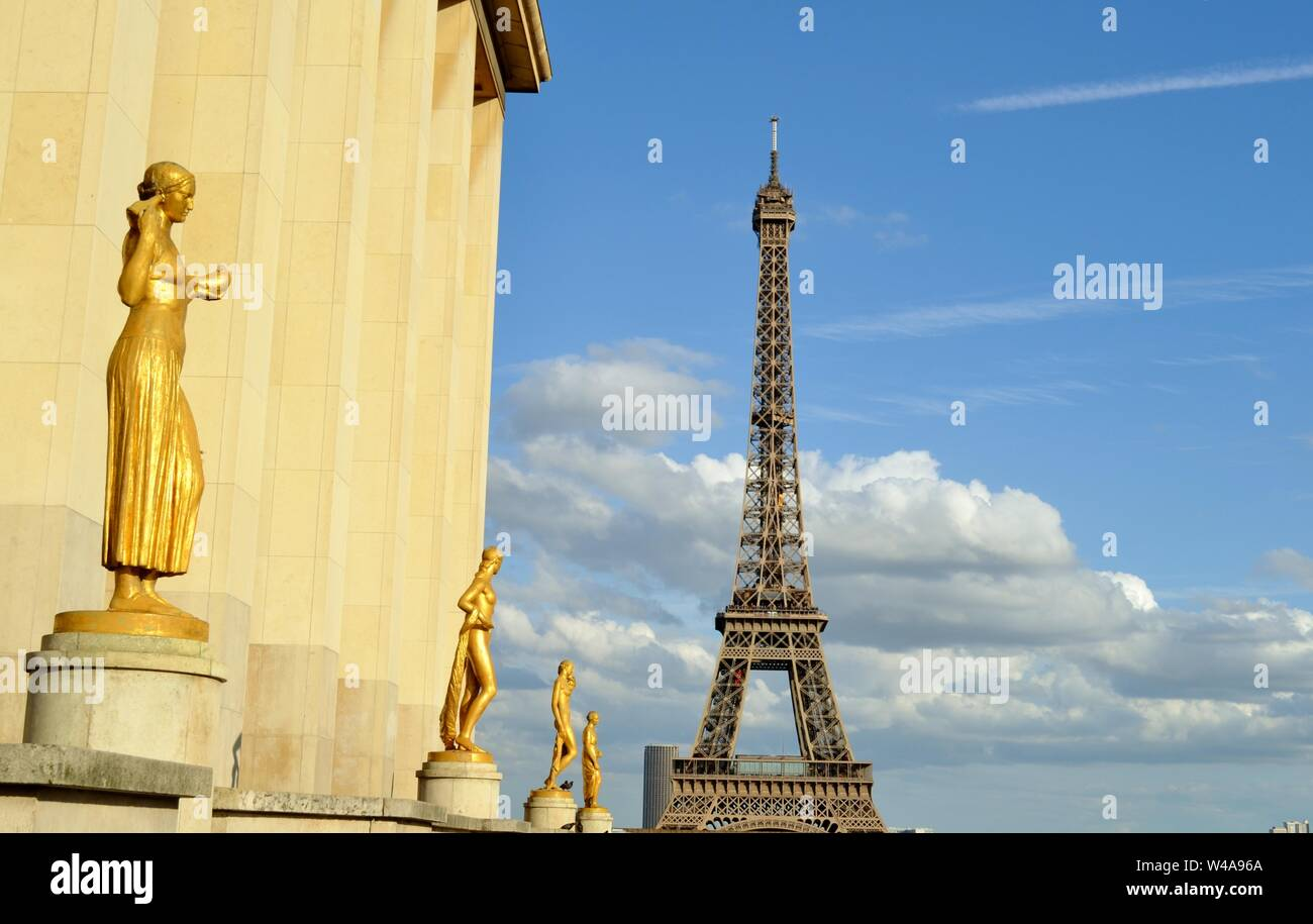 Beautiful golden statues at the Trocadero terrace in Paris with the Eiffel Tower with the blue sky and the white clouds background. Stock Photo