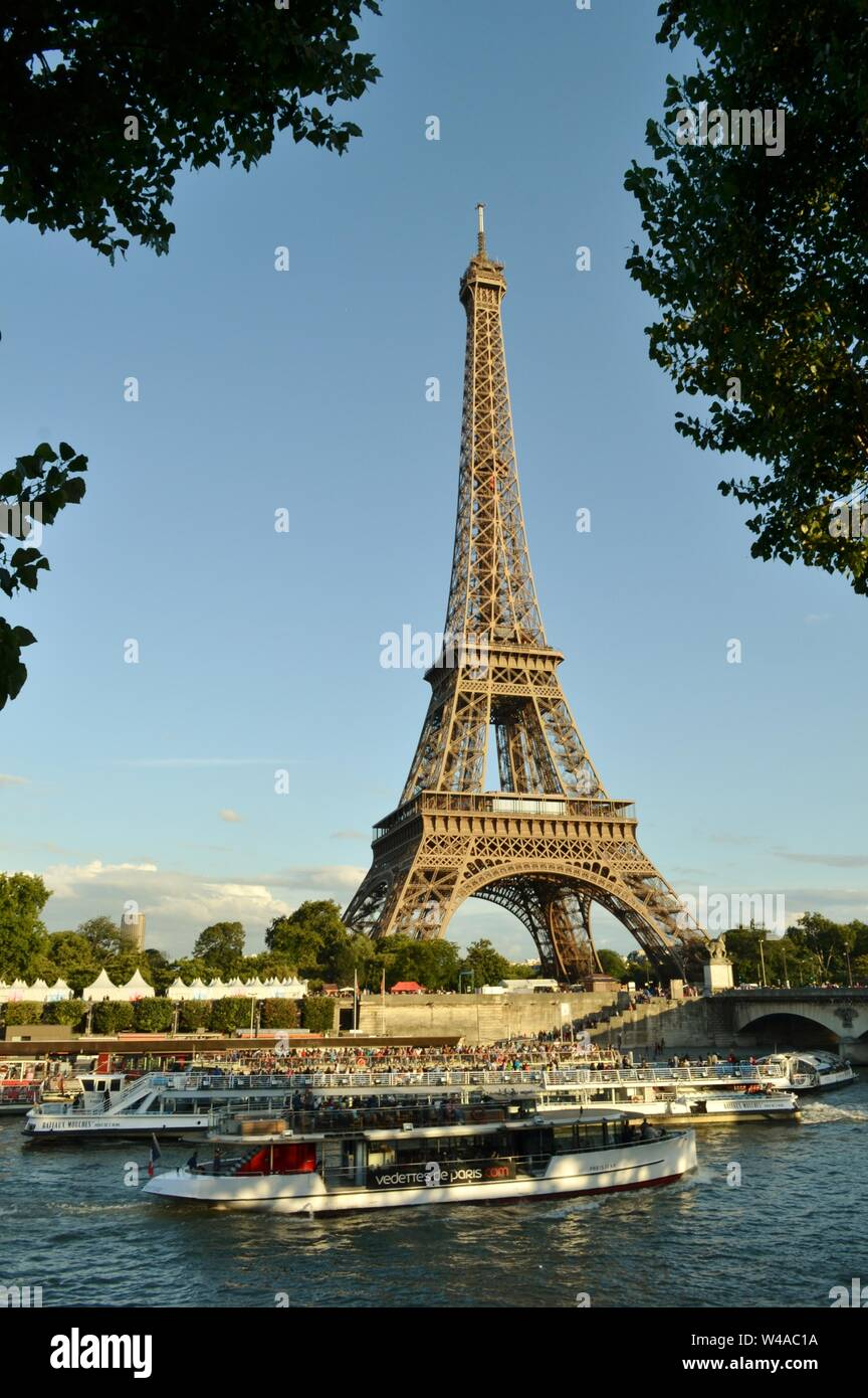 Paris/France - August 18, 2014: Beautiful panoramic view to the Eiffel Tower and river Seine intense cruise passenger ships traffic in a sunny day. Stock Photo