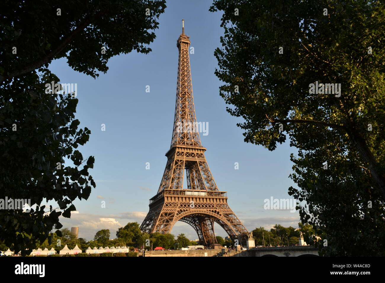 Beautiful panoramic view to the Eiffel Tower from the opposite Seine riverbank in a sunny summer day. Stock Photo