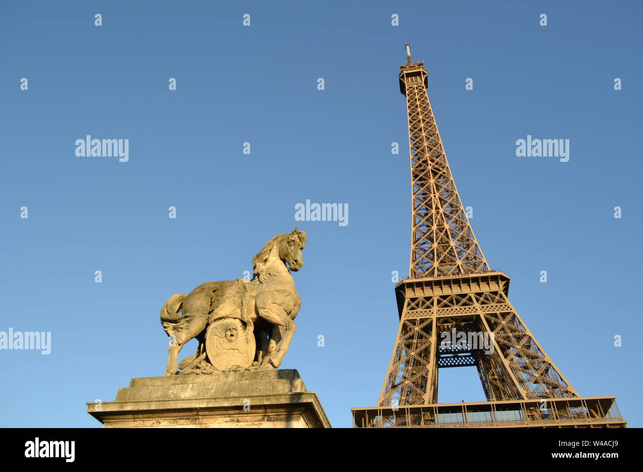 Sculpture of a horse on the Jena bridge in Paris and the Eiffel Tower in the background in a bright sunny day. Stock Photo