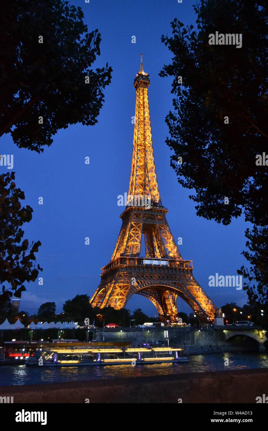 Beautiful panoramic view to the Eiffel Tower illuminated by night and the river Seine intense cruise passenger ships traffic. Stock Photo