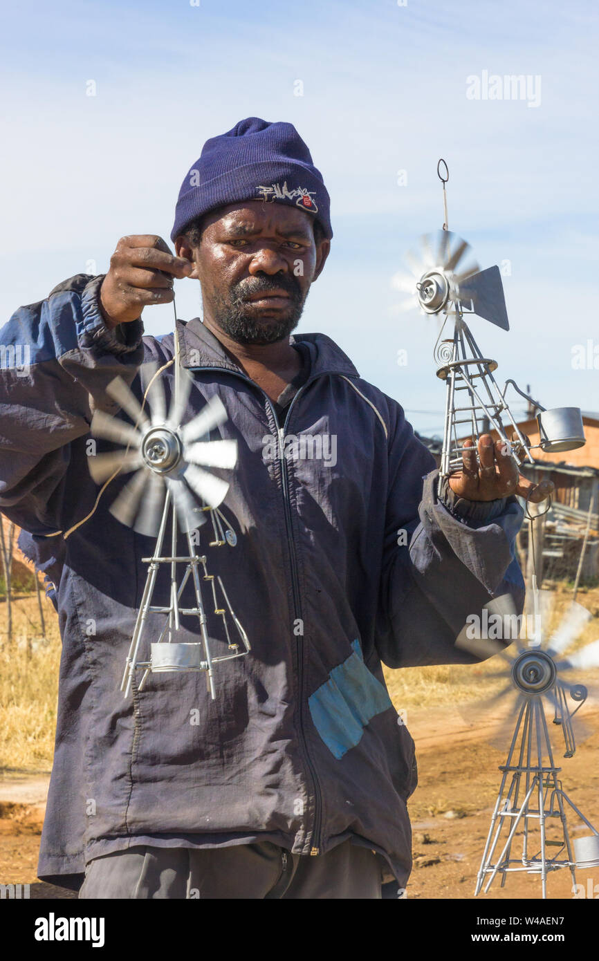 Black African poor street vendor selling hand made metal wind pumps on the side of the road to make some money to ease poverty in South Africa Stock Photo
