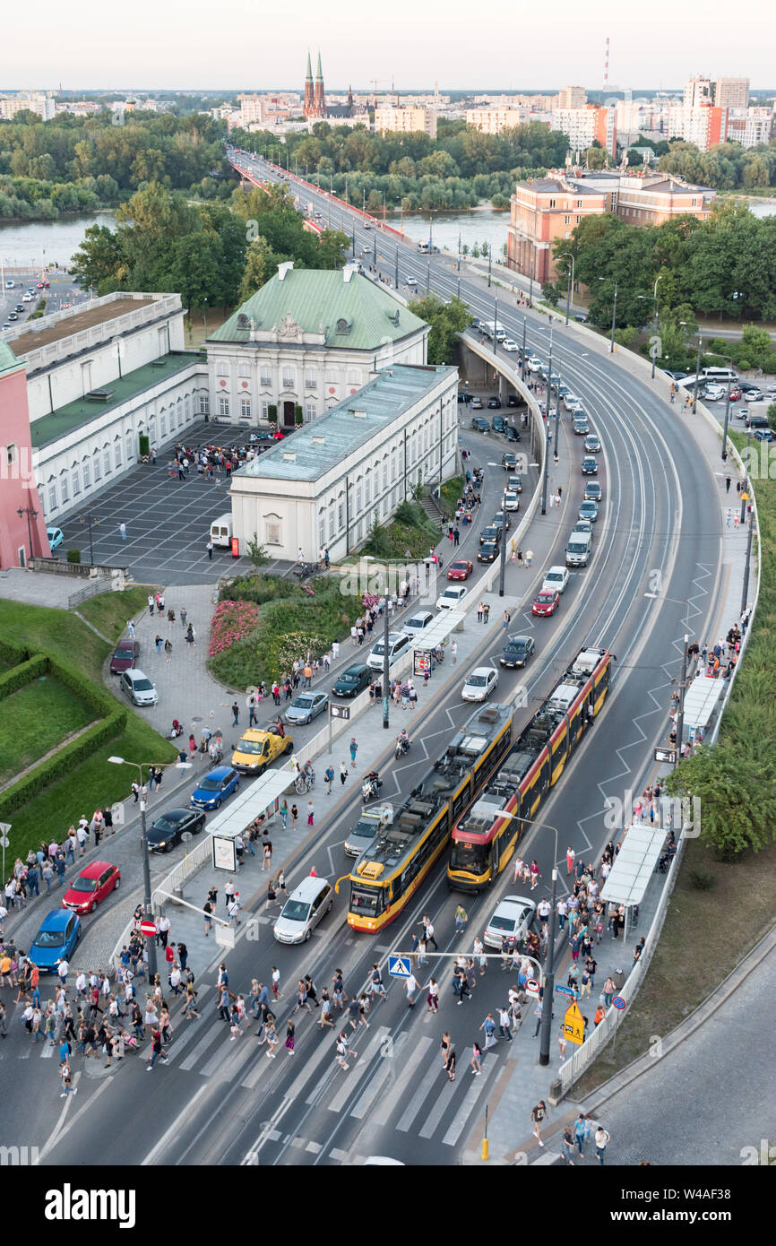 Queues of cars form as more than a hundred people exit trams and cross the road at the Stare Miasto tram stop near Castle Square in Warsaw's Old Town. Stock Photo