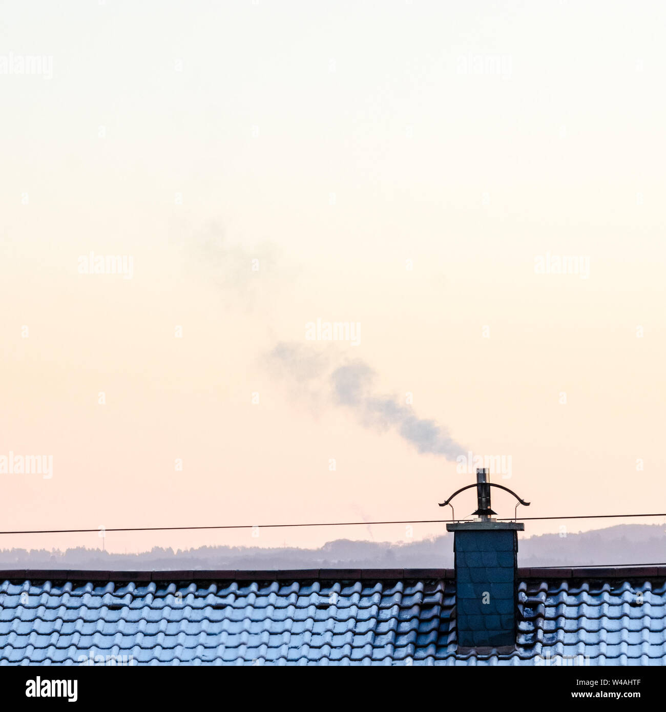 Smoking chimney on a roof during winter in Bavaria, Germany Stock Photo