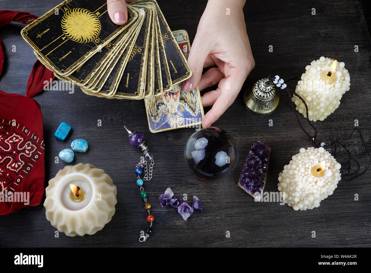 Fortune teller female hands and tarot cards on dark wooden table. Divination concept. Stock Photo