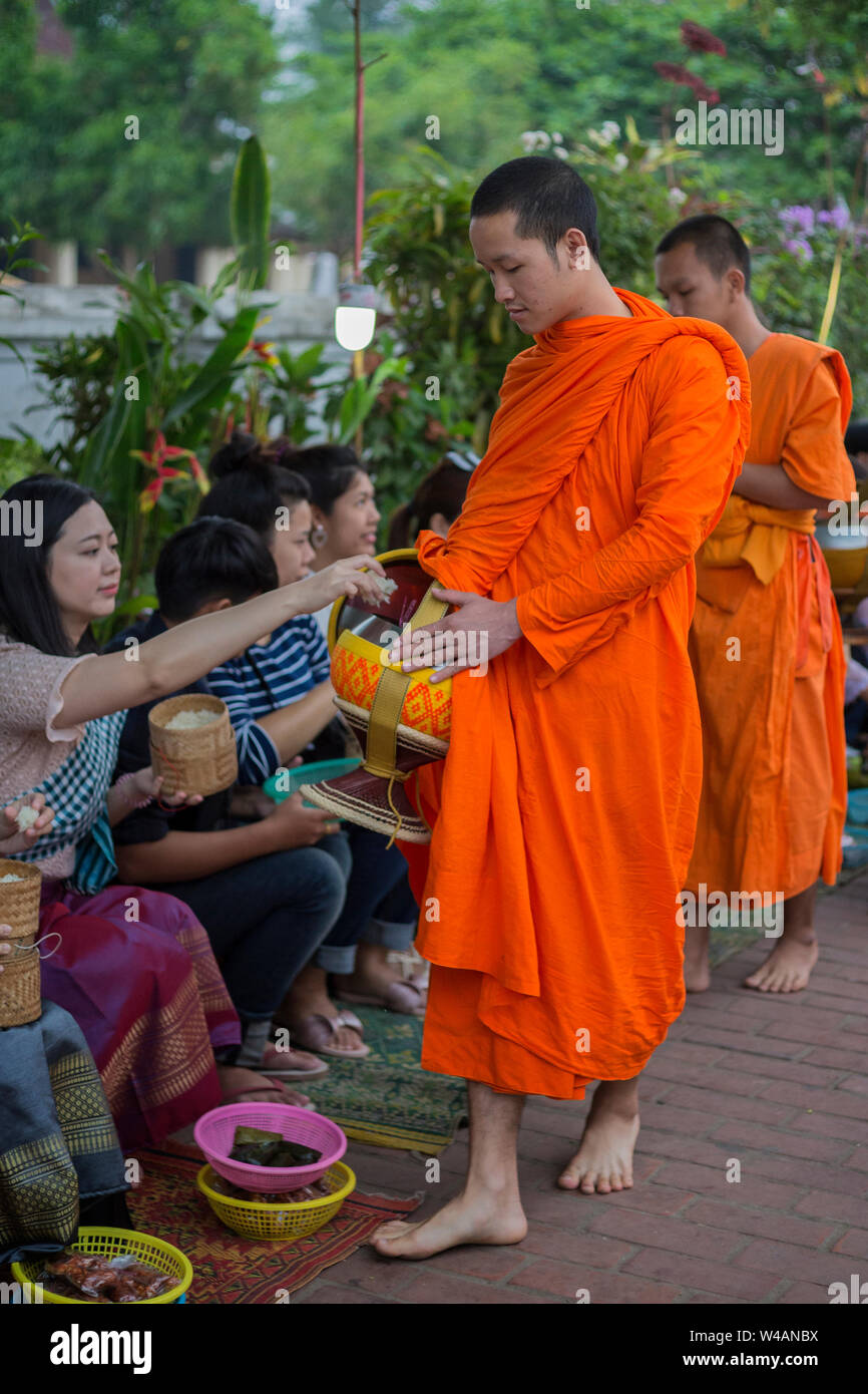 People giving alms to young Buddhist monks on the street early in the morning in Luang Prabang, Laos. The ritual is called Tak Bat. Stock Photo