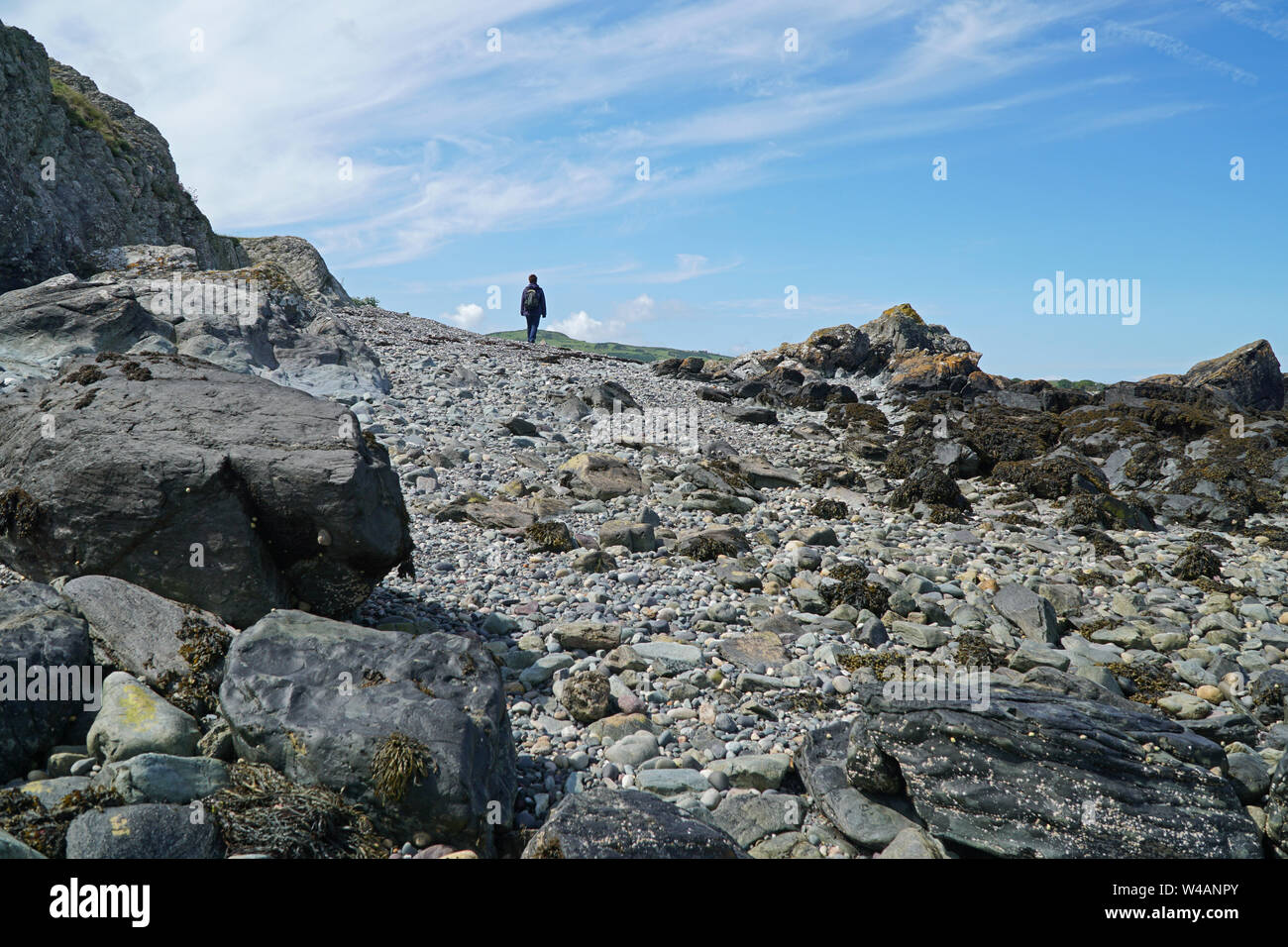 A lone woman walking on a rocky shore on a sunny day Stock Photo