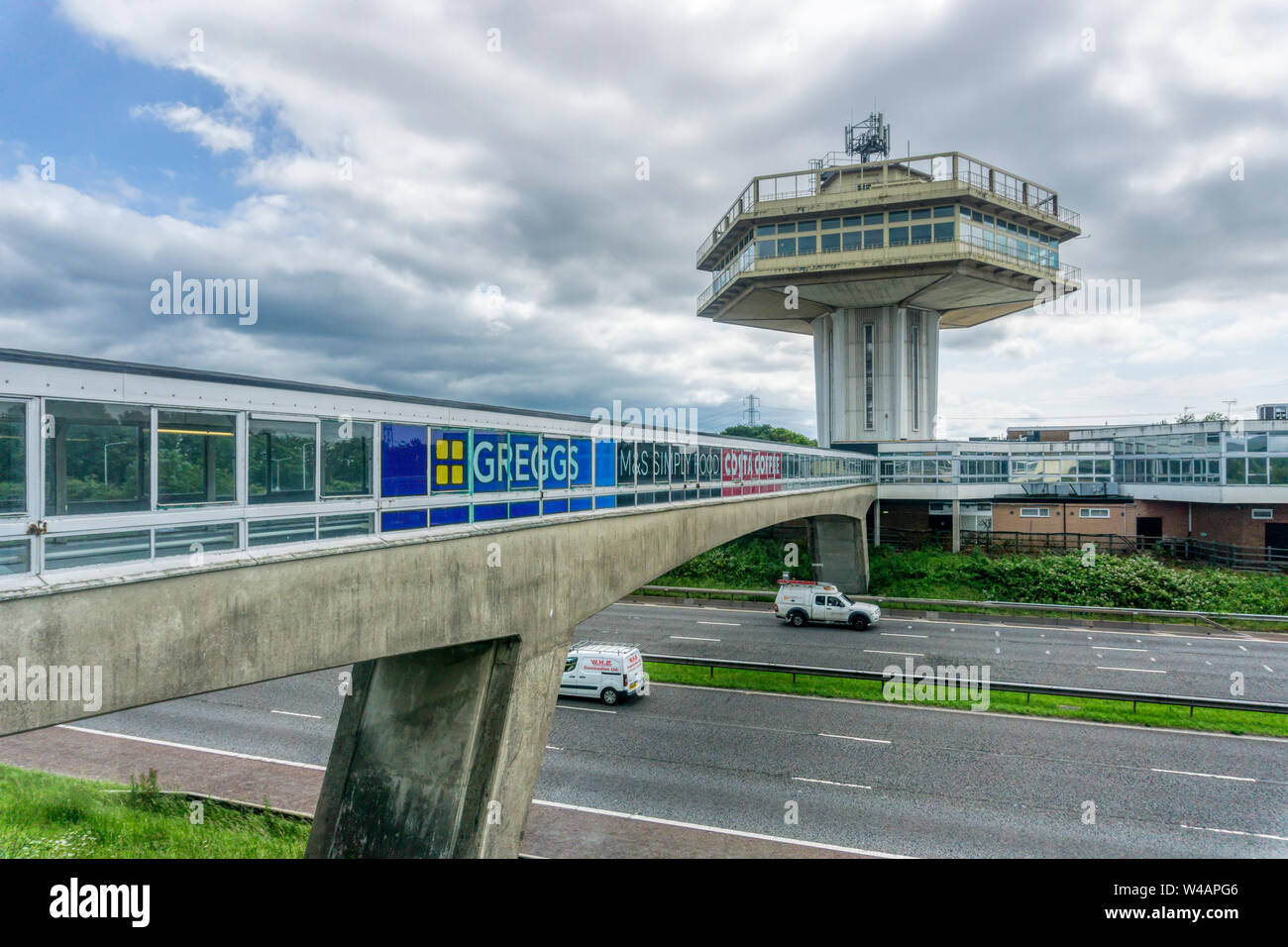 Brutalist architecture of the all weather enclosed bridge across the M6 motorway and the Pennine Tower of Lancaster Forton Services opened in 1965. Stock Photo