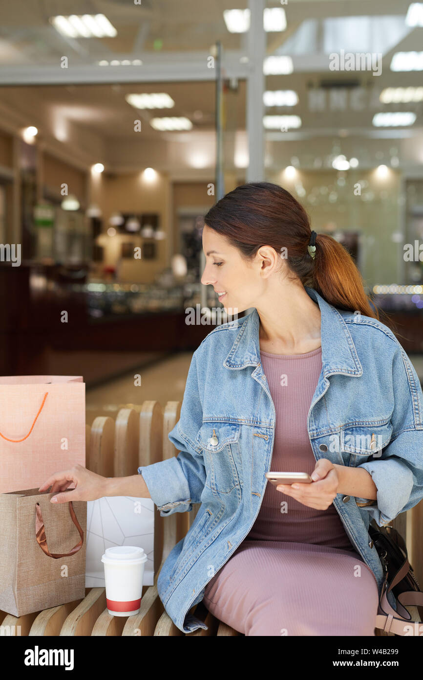 Young Attractive Girl In Denim Jacket Sitting On Bench Covered By Various Shopping Bags In Mall Stock Photo Alamy