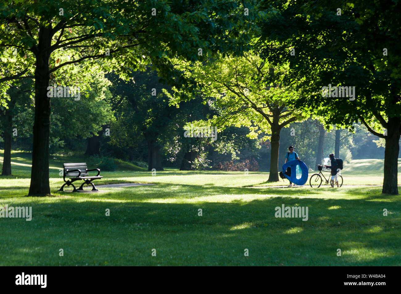 A Young Man With Camping Gear And A Young Woman With A Bike In A Park Early In The Morning Canada Ideal Setting For Meditation Jogging Or A Picnic Stock Photo
