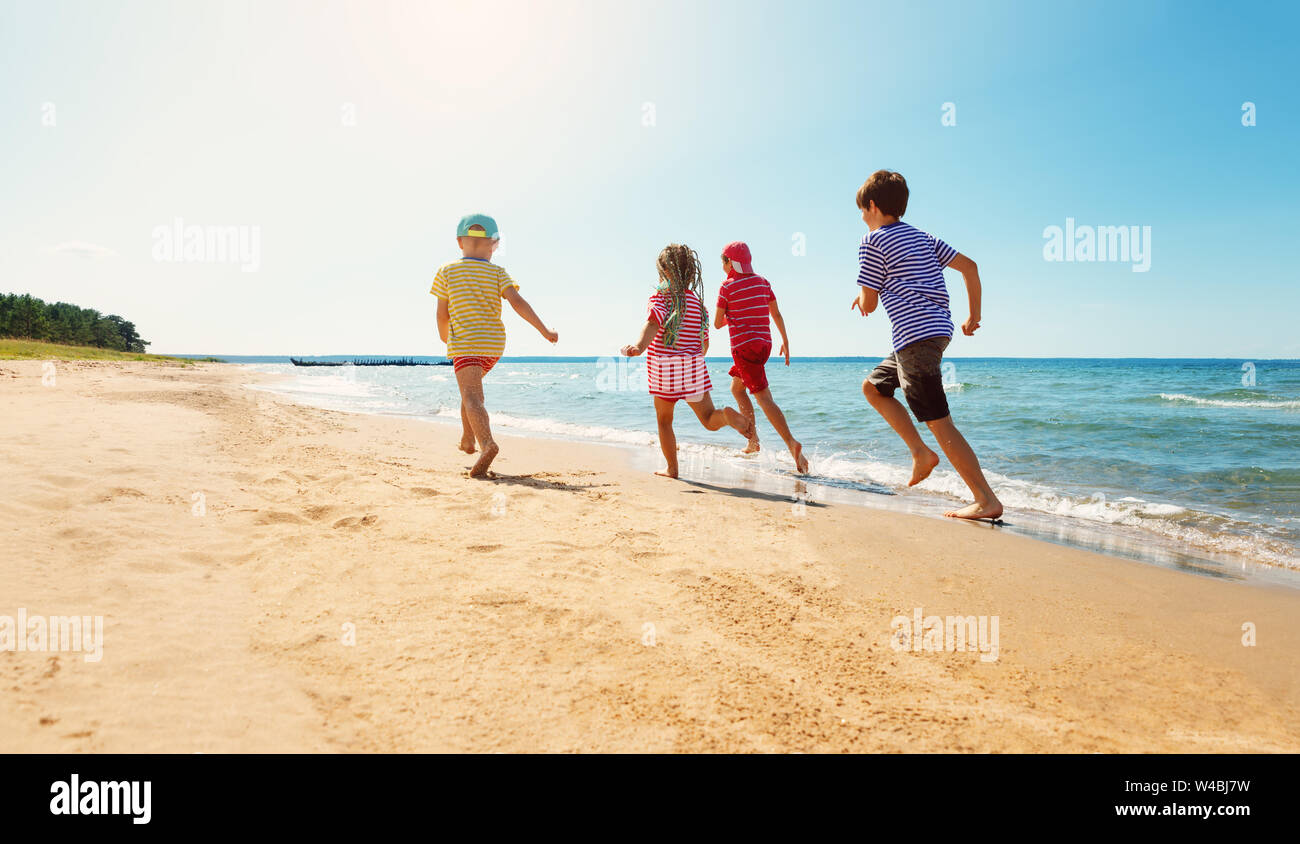 Happy kids on vacations at seaside running in the water Stock Photo