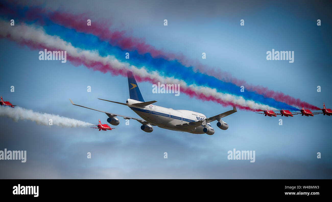 Flypast by the RAF Red Arrows aerobatic display team in formation with a BOAC liveried Boeing 747 at The Royal International Air Tattoo, Fairford, UK Stock Photo