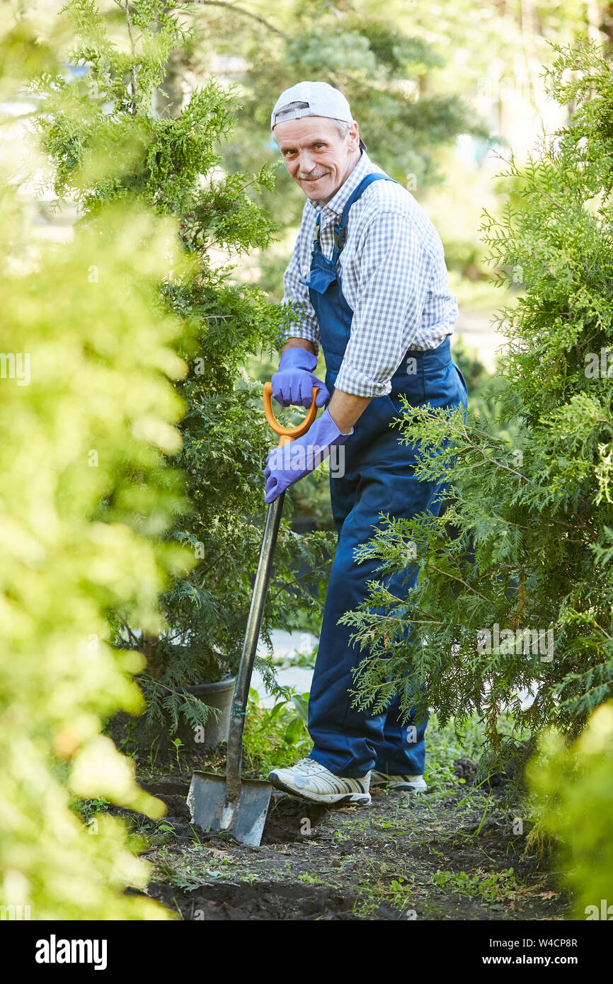 Full length portrait of smiling mature man working in garden and looking at camera Stock Photo