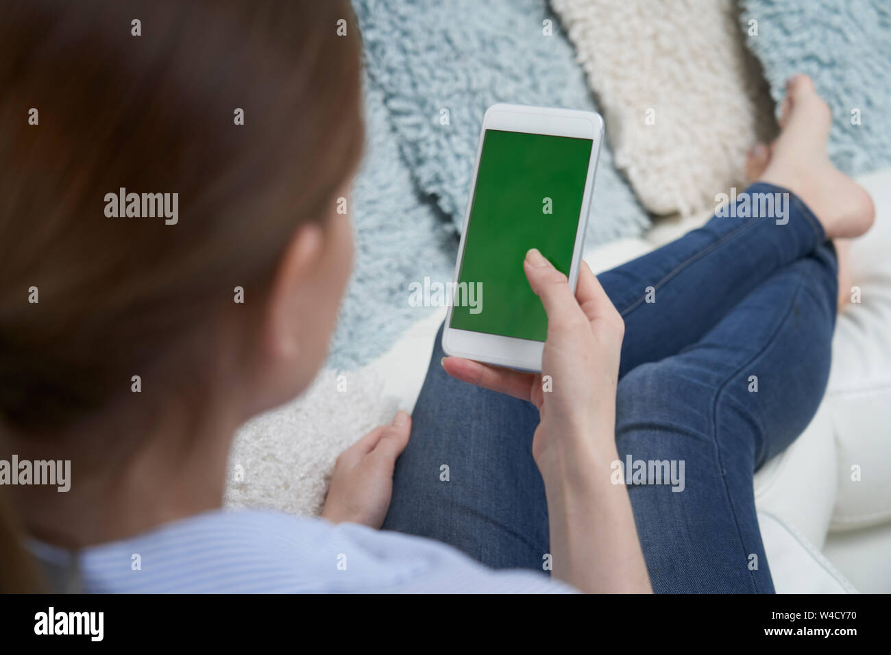 Over The Shoulder View Of Woman Lying On Sofa Using Green Screen Mobile Phone At Home Stock Photo