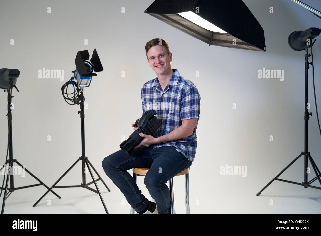 Portrait Of Male Photographer In Studio For Photo Shoot With Camera And Lighting Equipment Stock Photo