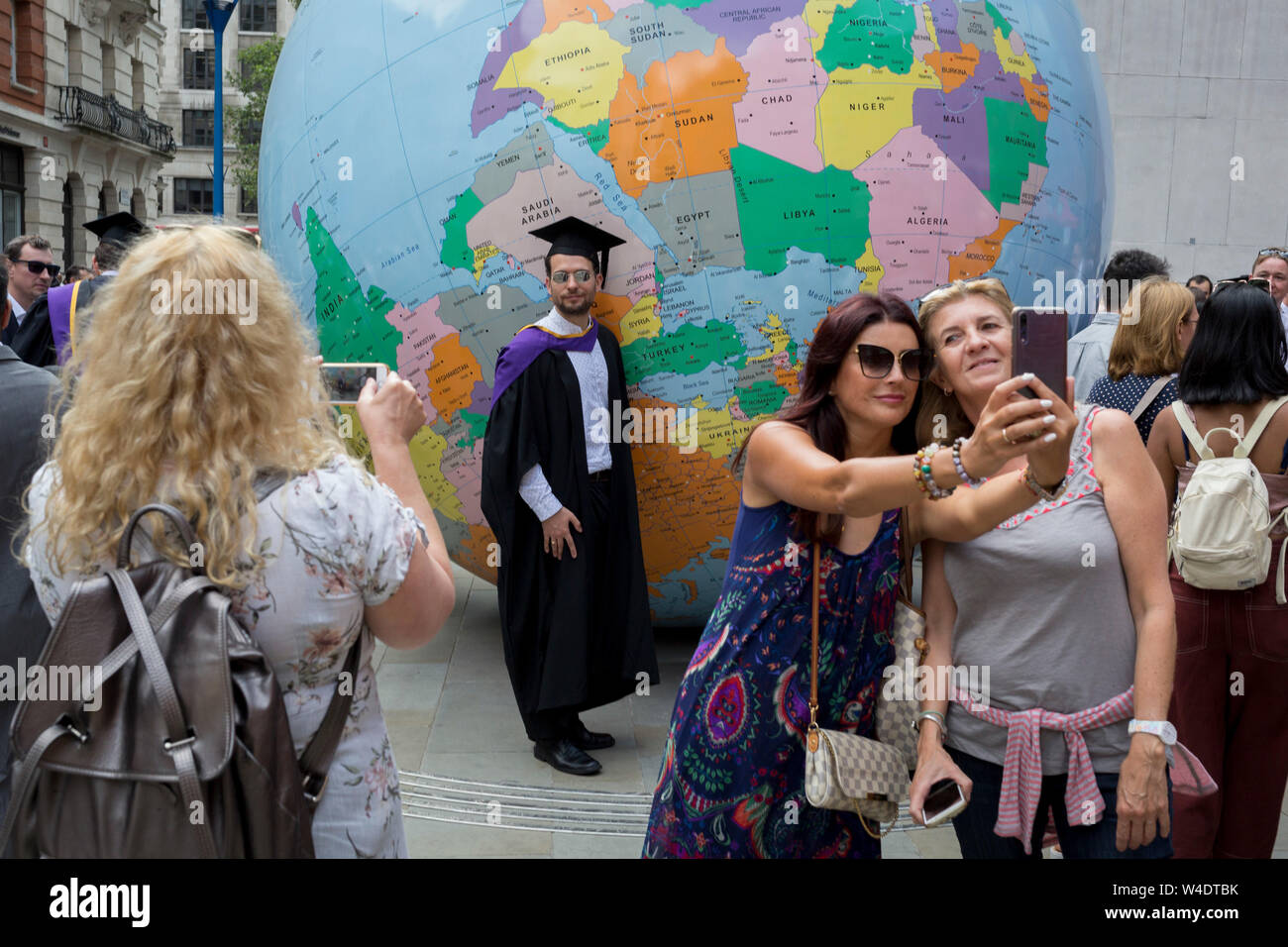 "Beneath the sculpture by Turner Prize-winning artist Mark Wallinger entitled ""The World Turned Upside Down', new graduates straight after their graduation ceremonies meet family and friends outside the London School of Economics (LSE), on 22nd July 2019, in London, England. 'The World Turned Upside Down' is a large political globe, four metres in diameter, with nation states and borders outlined but with the simple and revolutionary twist of being inverted. Most of the landmasses now lie in the 'bottom' hemisphere with the countries and cities re-labelled for this new orientation. Stock Photo"