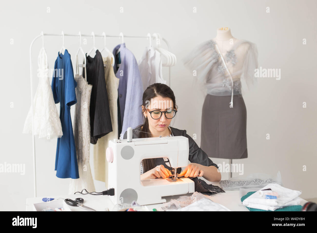 Dressmaker Tailor And Fashion Concept Smiling Female Fashion Designer Using Sewing Machine And Sitting Behind Her Desk Stock Photo Alamy