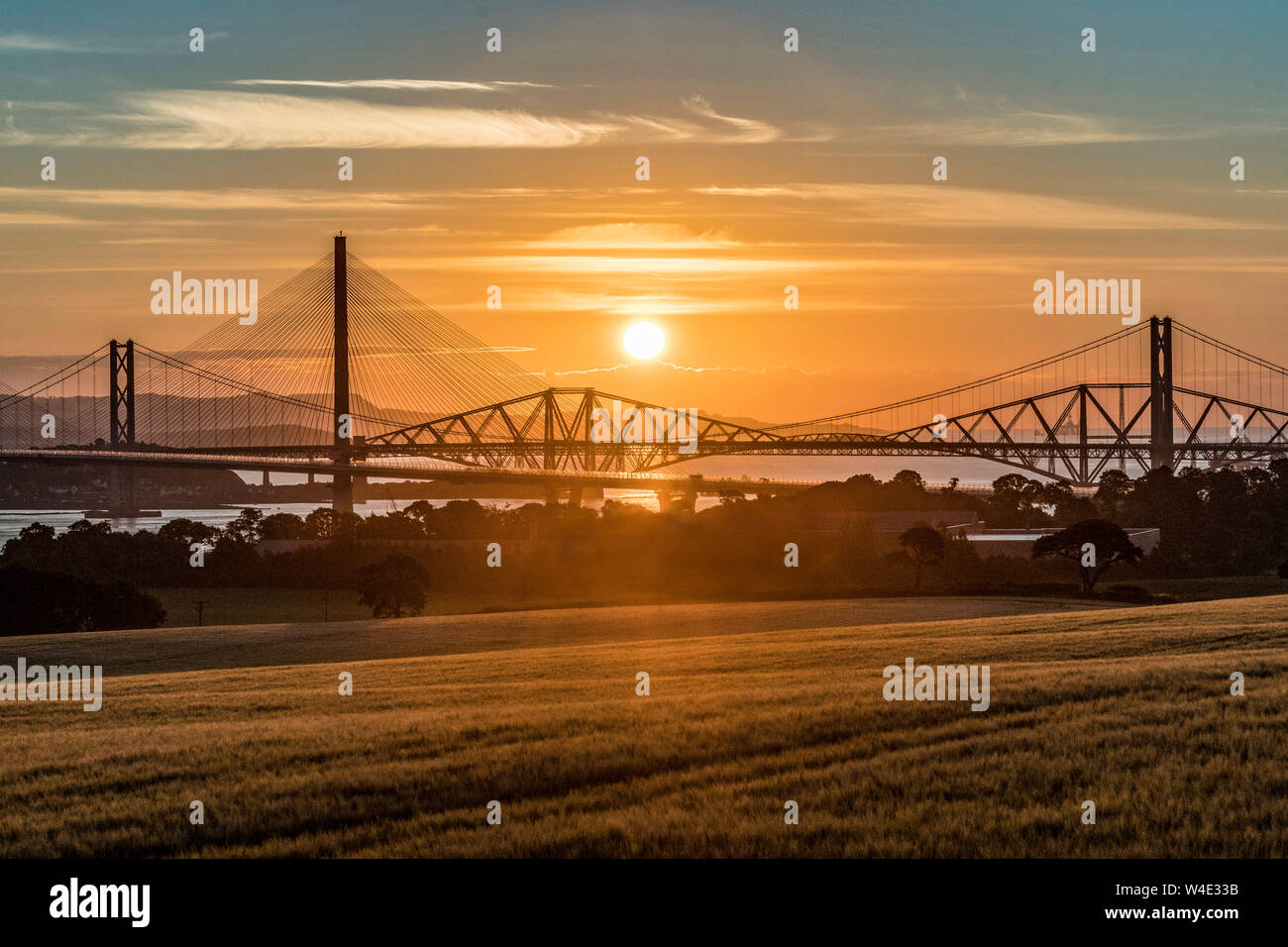 Queensferry Crossing at sunrise with the three Forth Bridges at South Queensferry Stock Photo
