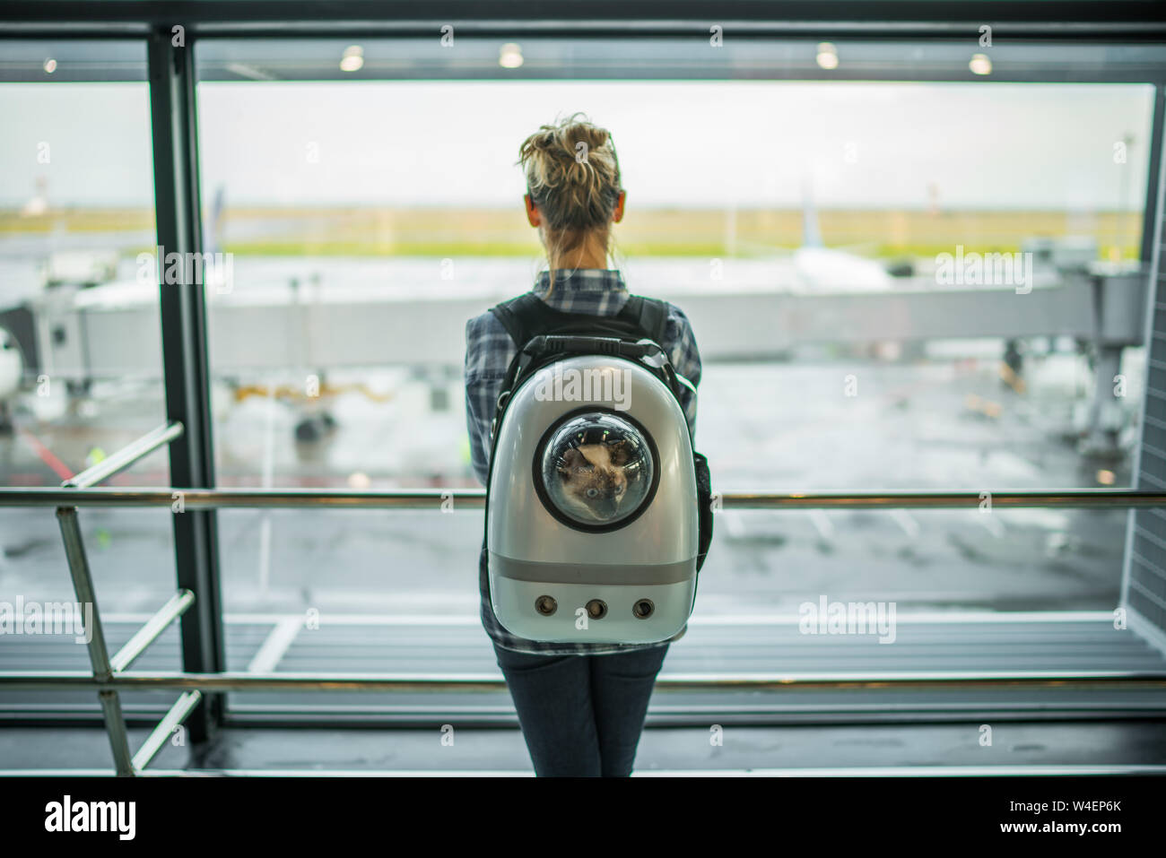 Woman wearing a space shuttle cat carrier on her back while