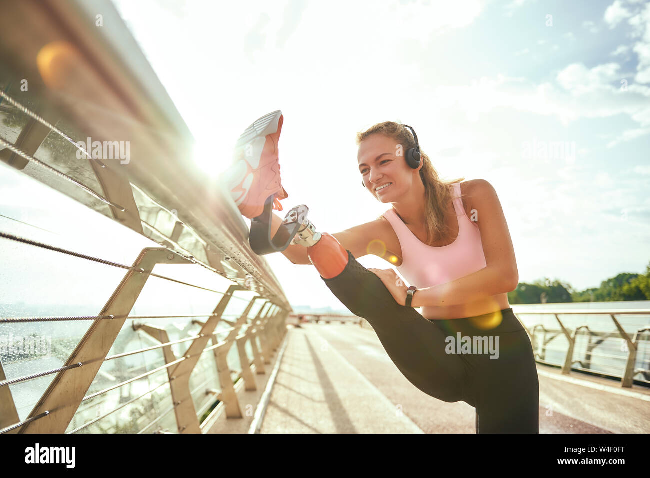 Disabled positive woman in sportswear and headphones