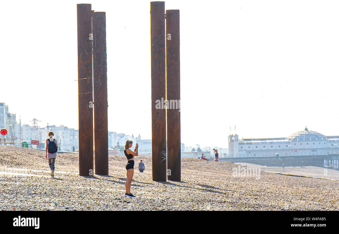 Brighton UK 23rd July 2019 - Visitors enjoy the early morning hot sunshine by the West Pier in Brighton . Heatwave conditions are forecast for the South East of Britain with temperatures expected to reach the mid thirties today and over the next few days . Credit: Simon Dack / Alamy Live News Stock Photo