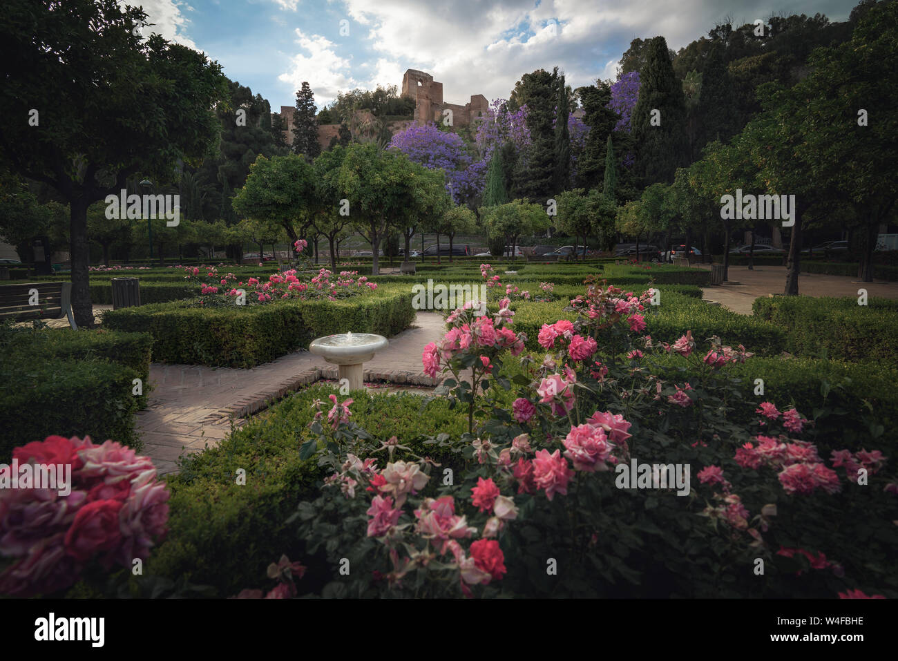 Flowers at Pedro Luis Alonso Gardens with Alcazaba Castle on background - Malaga, Andalusia, Spain Stock Photo