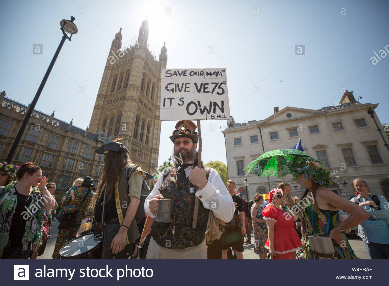London, UK. 23rd July 2019. Morris dancers protest outside Parliament in Westminster over the Government's decision to move next year's May Day bank holiday from its traditional Monday to the following Friday. The move switches the holiday to May 8th in order to celebrate the 75th anniversary of VE Day. Morris Dancers claim the switch will disrupt hundreds of festivals and events nationwide, harming local economies. Morris Dancers are requesting an additional Bank Holiday instead. Credit: Guy Corbishley/Alamy Live News Stock Photo