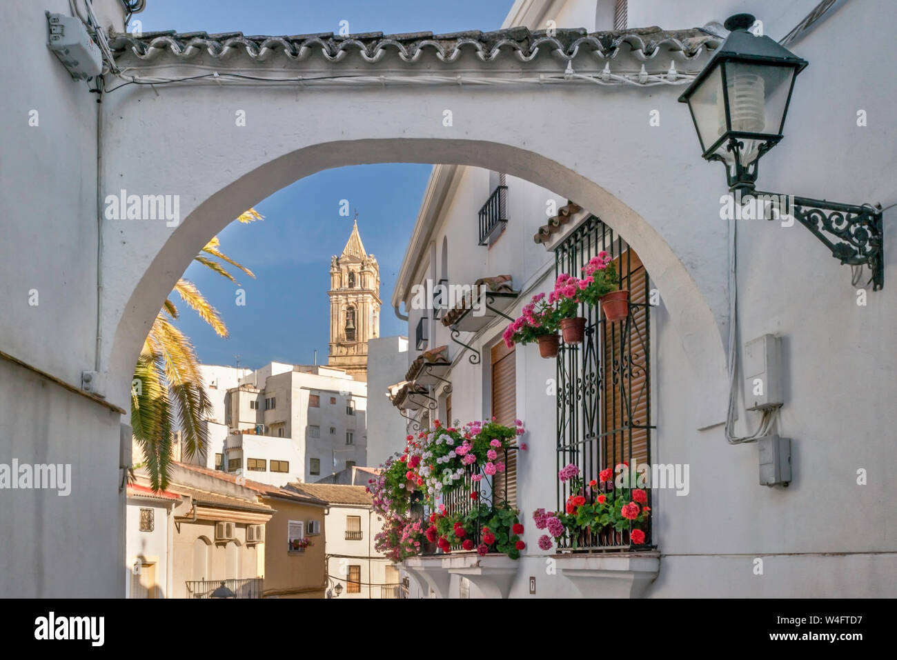 Cuesta de San Juan, alleyway with buttress between buildings, Iglesia de la Asuncion in distance, in Cabra, Cordoba Province, Andalusia, Spain Stock Photo