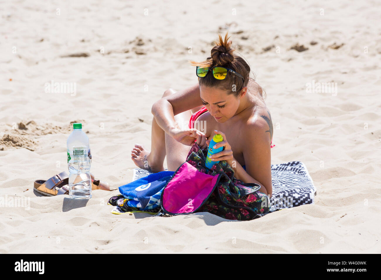 Bournemouth, Dorset UK. 23rd July 2019. UK weather: thousands flock to the beaches at Bournemouth during the heatwave on a scorching hot and sunny day. Reaching for the suncream. Credit: Carolyn Jenkins/Alamy Live News Stock Photo