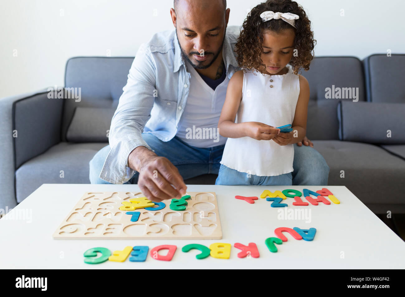 Father and daughter playing with alphabet learning game at home Stock Photo