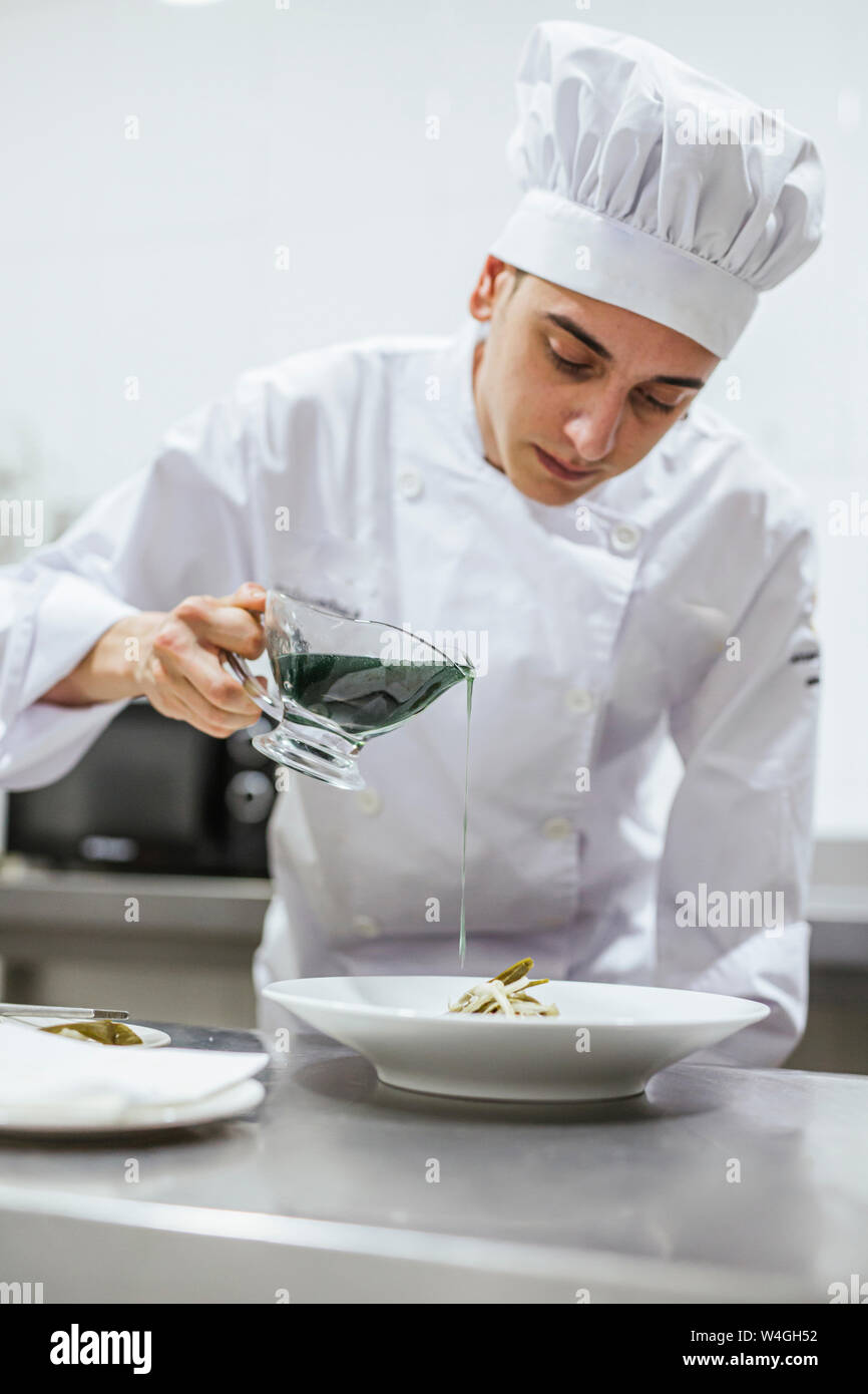 Junior chef prepairing a meal on plate Stock Photo