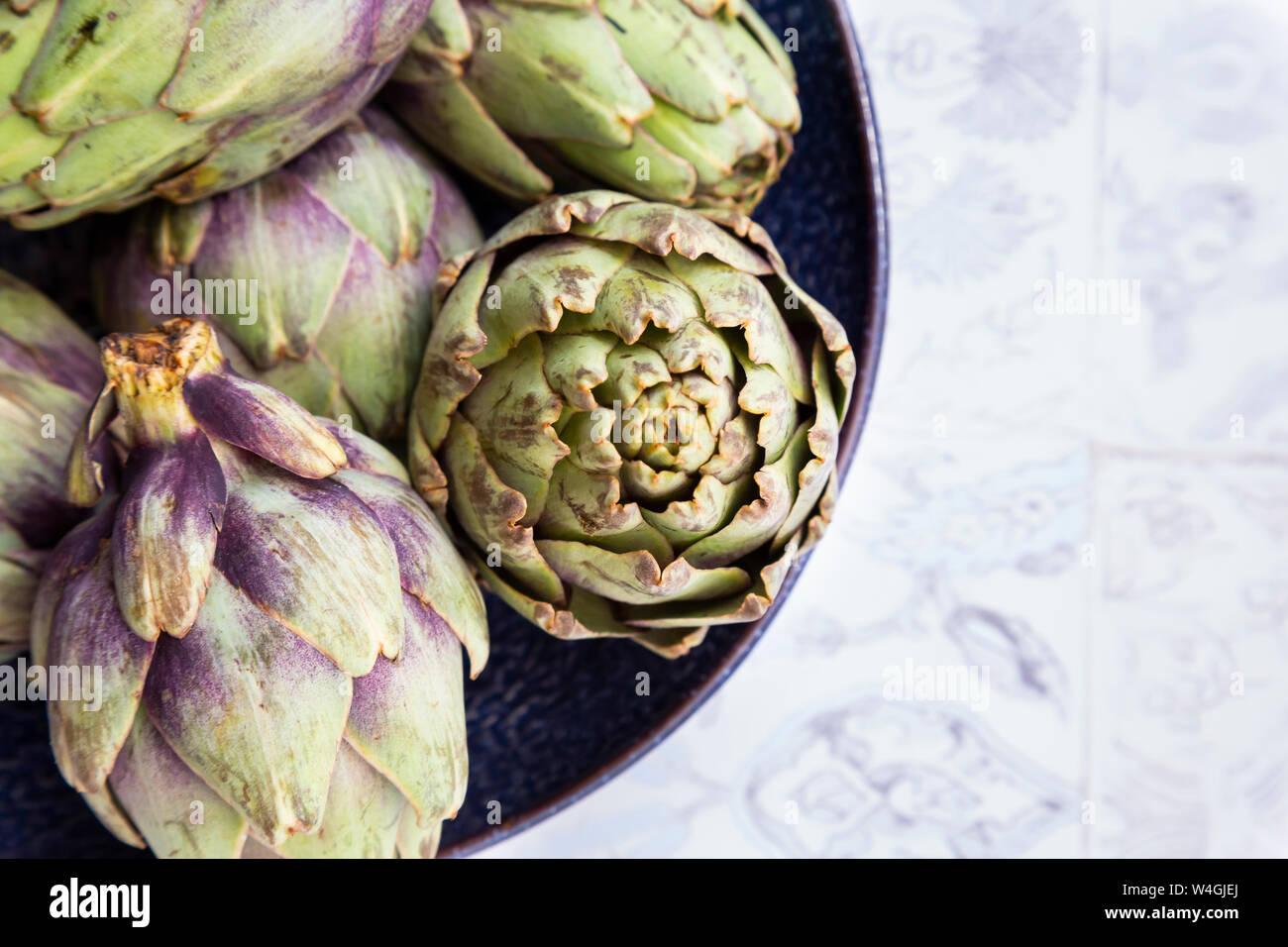 Italian bio artichokes in bowl, from above Stock Photo