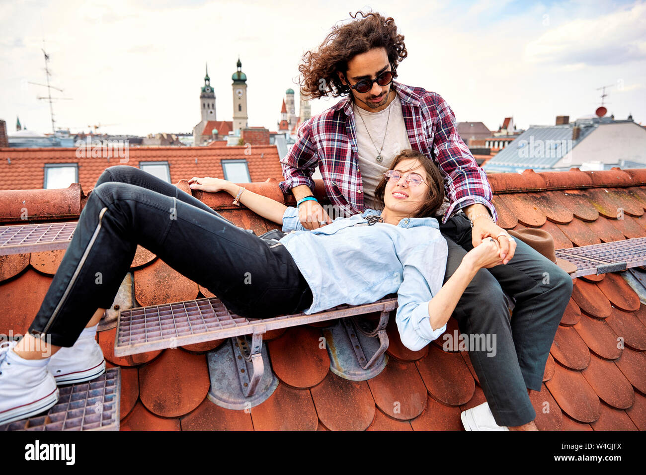 Young couple relaxing on rooftop Stock Photo